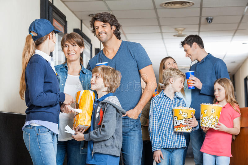 Trabalhador com as famílias no cinema foto de stock