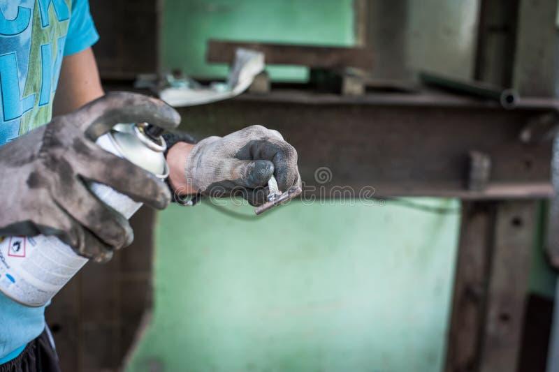 Trabalhador com as luvas protetoras que pintam a peça de metal foto de stock royalty free