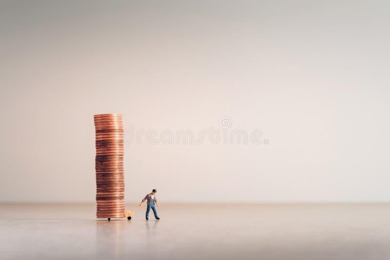 Trabalhador com caminhão de mão completamente das moedas imagens de stock