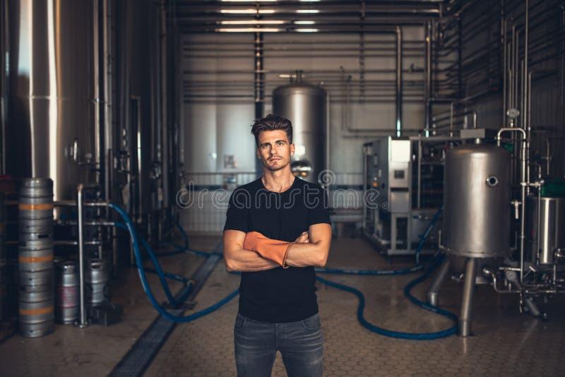 Trabalhador com equipamento industrial na cervejaria imagens de stock