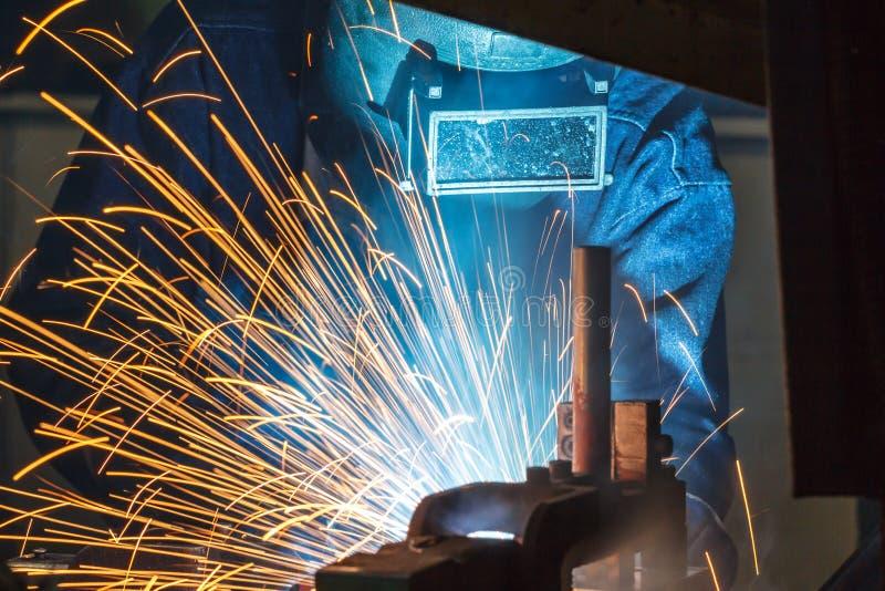 Trabalhador com metal de soldadura da máscara protetora fotografia de stock
