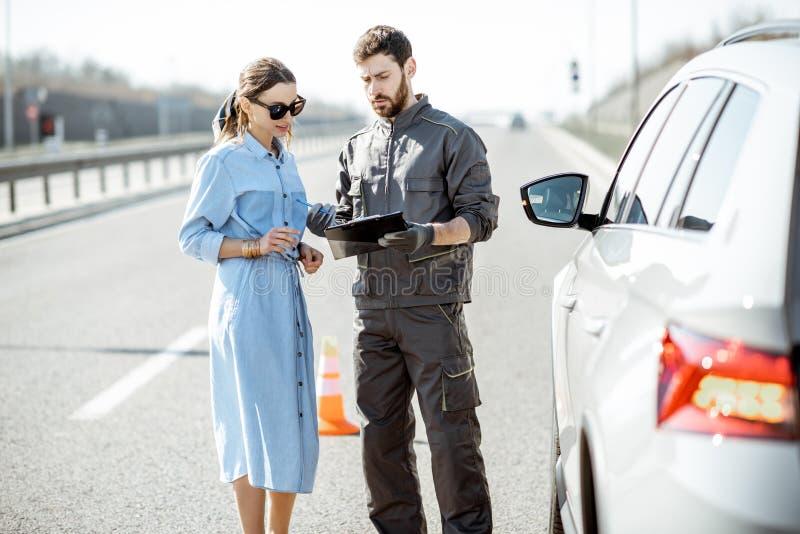 Trabalhador com a mulher perto do carro quebrado na estrada foto de stock royalty free