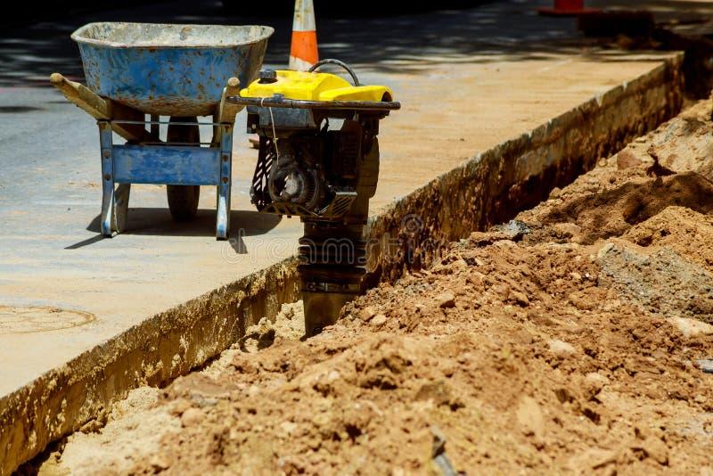 Trabalhador com o equipamento da broca de martelo pneumático que quebra o asfalto no local da construção de estradas imagem de stock