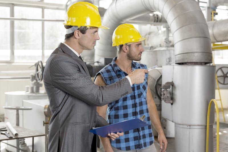 Trabalhador com o supervisor que inspeciona a área industrial fotografia de stock royalty free