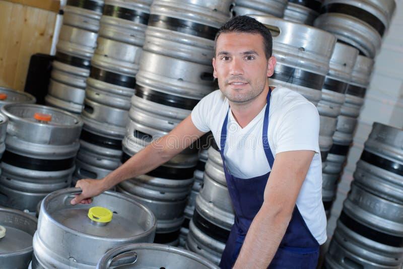 Trabalhador com os tambores de cerveja na cervejaria foto de stock royalty free