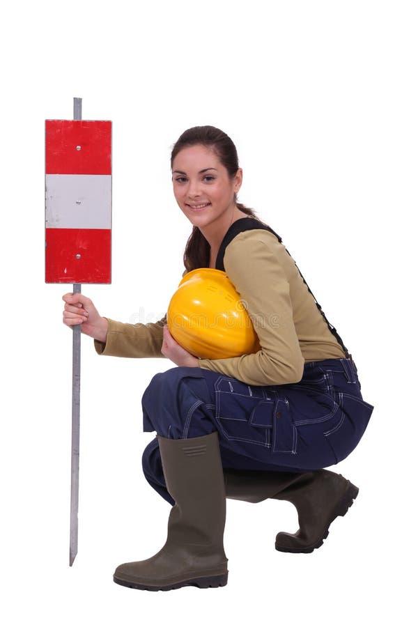 Trabalhador com um sinal de aviso imagem de stock royalty free