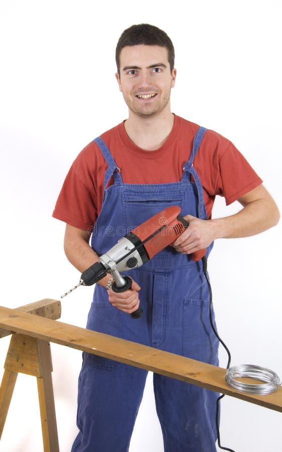 Trabalhador com uma broca em suas mãos foto de stock