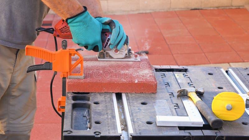 Trabalhador cortando azulejos para colocar no terraço usando serra circular elétrica fotos de stock