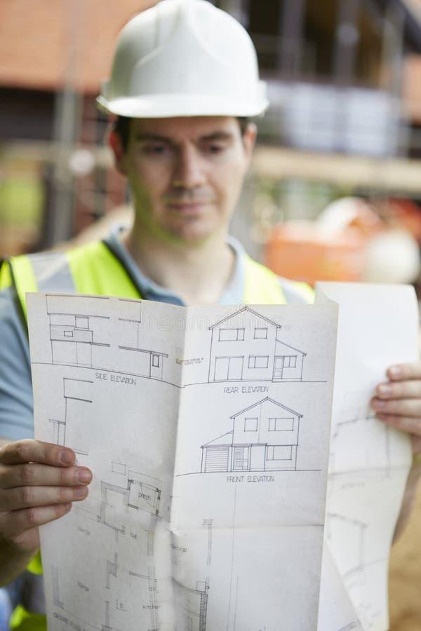 Trabalhador da construção On Building Site que olha planos da casa imagem de stock royalty free