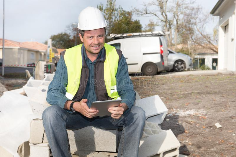Trabalhador da construção caucasiano masculino que senta-se com tabuleta imagem de stock