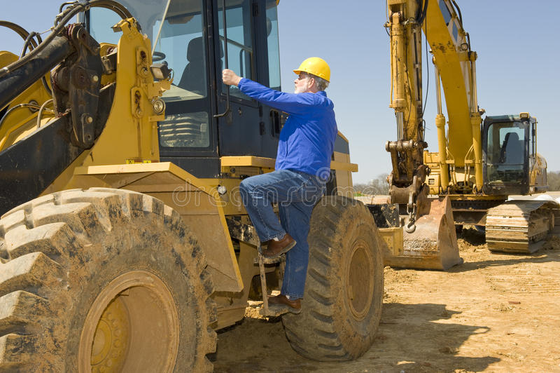 Trabalhador da construção Climbing Heavy Equipment foto de stock