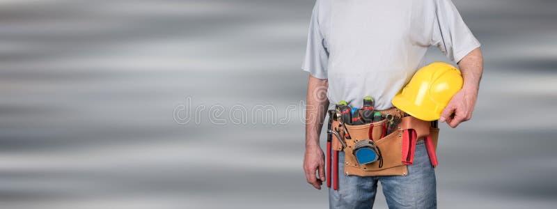 Trabalhador da construção com correia e capacete da ferramenta imagem de stock