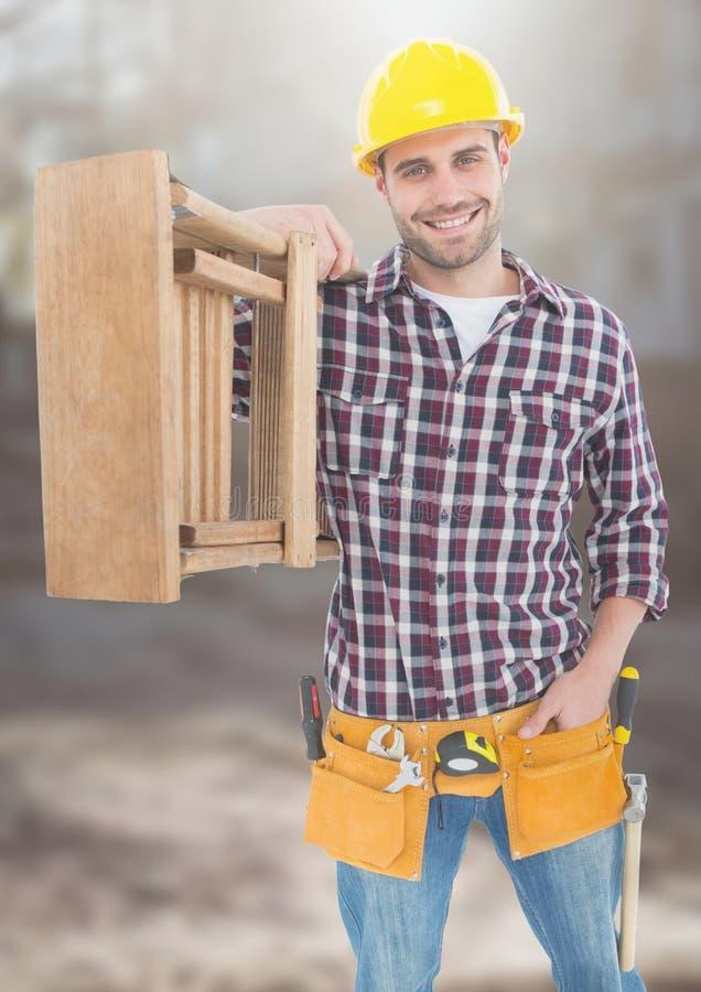 Trabalhador da construção com a escada na frente do canteiro de obras fotografia de stock