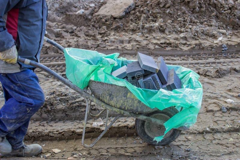 Trabalhador da construção com os tijolos no carrinho de mão imagens de stock
