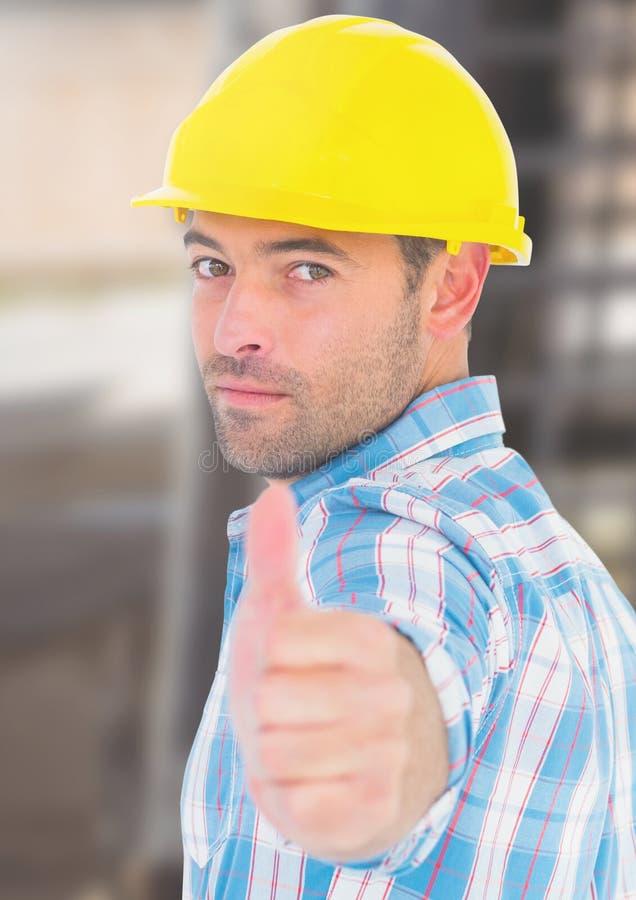 Trabalhador da construção com polegares acima na frente do canteiro de obras fotografia de stock royalty free