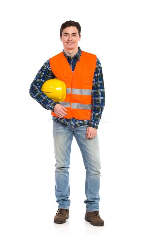Trabalhador da construção de sorriso com o capacete sob o braço. fotos de stock royalty free