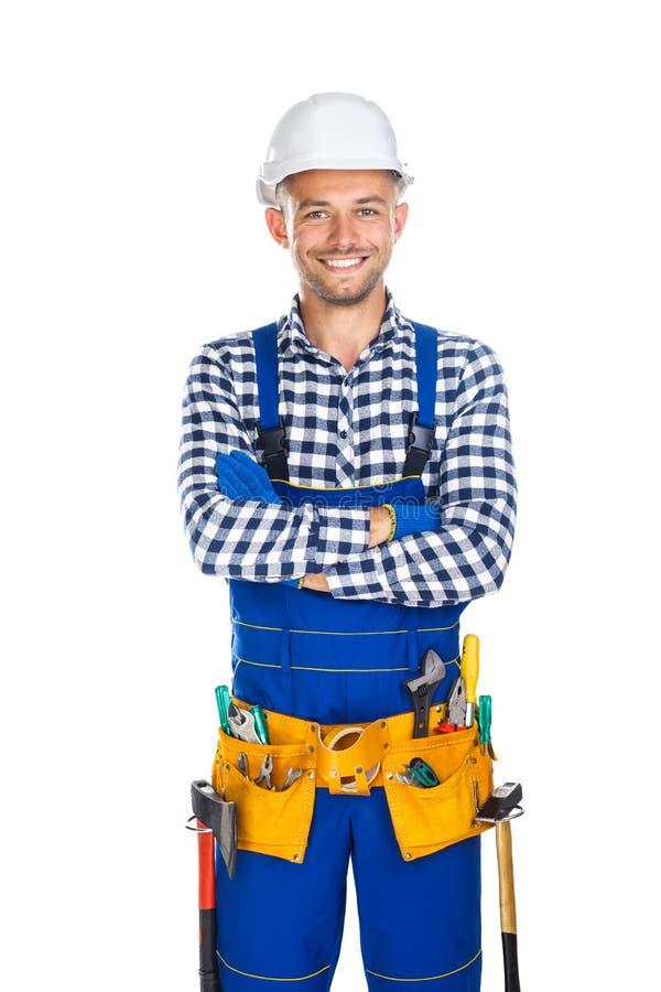 Trabalhador da construção de sorriso feliz na correia do uniforme e da ferramenta com foto de stock