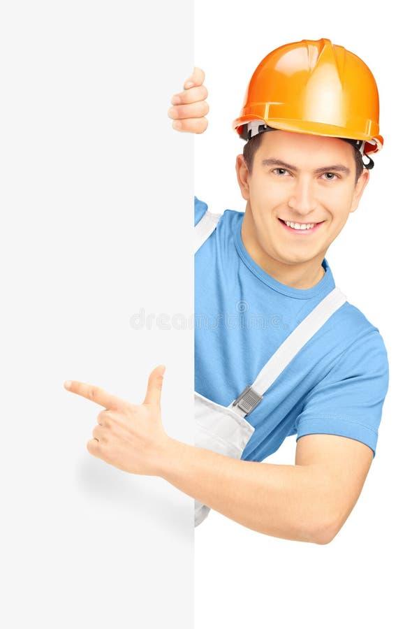 Trabalhador da construção de sorriso novo com capacete que aponta no painel fotografia de stock royalty free