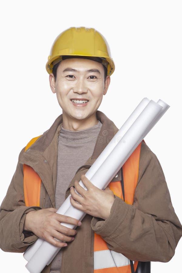 Trabalhador da construção de sorriso que mantem o modelo contra o fundo branco, retrato, olhando a câmera fotografia de stock royalty free