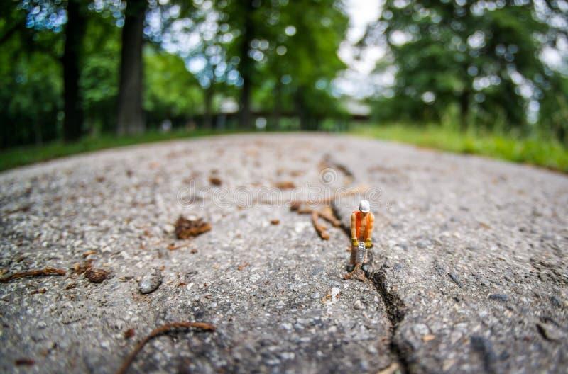 Trabalhador da construção diminuto com o martelo da broca na quebra no asfalto foto de stock royalty free
