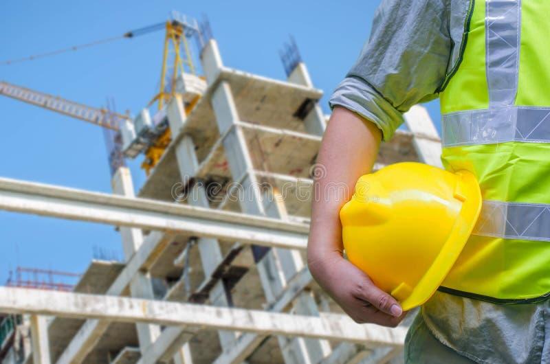 Trabalhador da construção do close-up que guarda o capacete de segurança com fundo de fotografia de stock royalty free