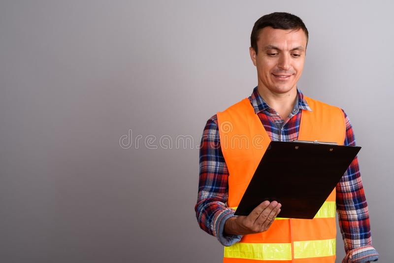 Trabalhador da construção do homem que mantém a prancheta contra o backgroun cinzento fotografia de stock