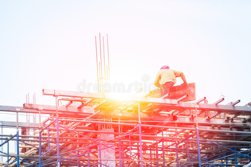Trabalhador da construção durante o trabalho do reforço com as hastes do rebar do metal no terreno de construção fotografia de stock royalty free