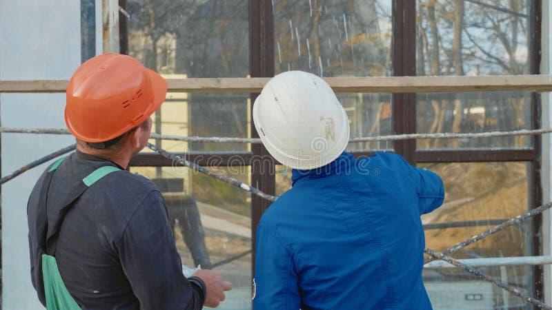 Trabalhador da construção e coordenador que falam no local do canteiro de obras, vista traseira imagens de stock