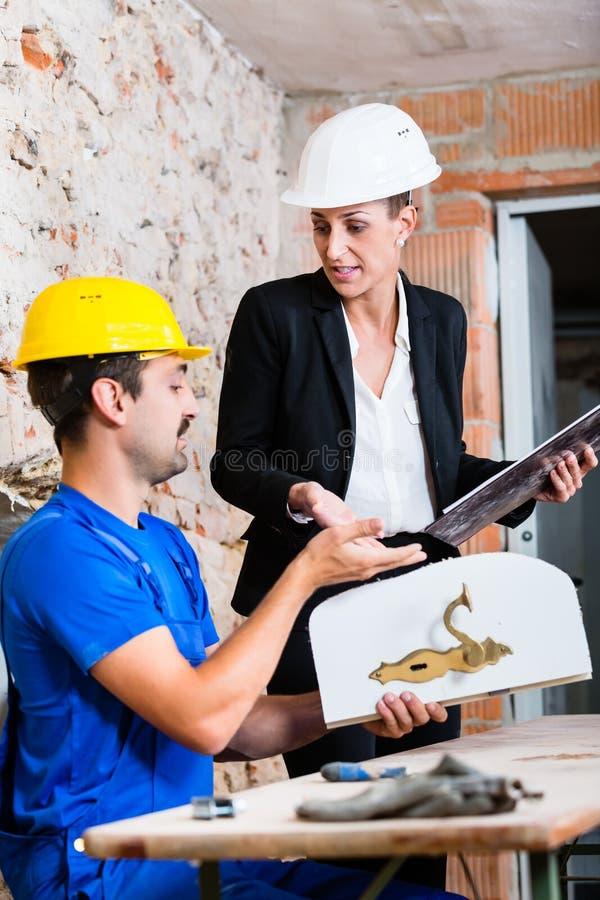 Trabalhador da construção e designer de interiores com porta foto de stock