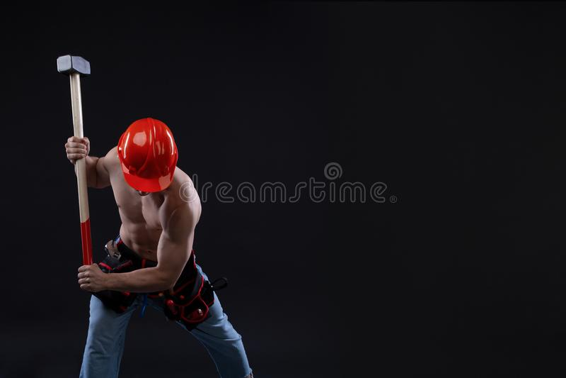 Trabalhador da construção em topless novo considerável com martelo de pequeno trenó, tiro do estúdio, fundo preto Construtor foto de stock royalty free