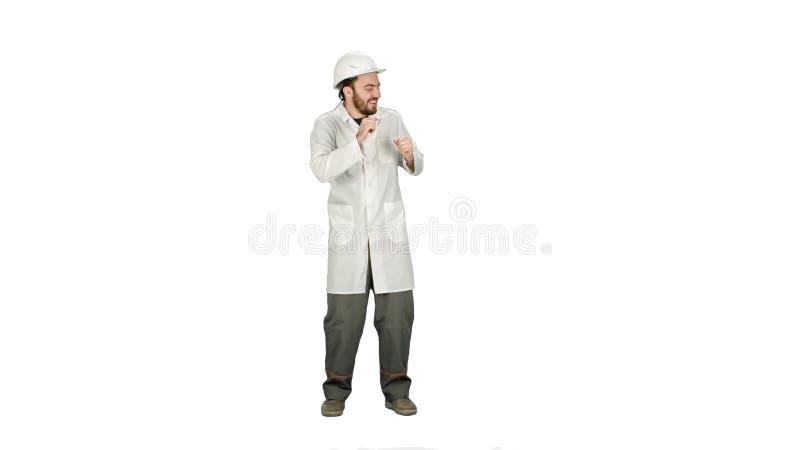 Trabalhador da construção engraçado da dança, arquiteto, eletricista no capacete no fundo branco filme