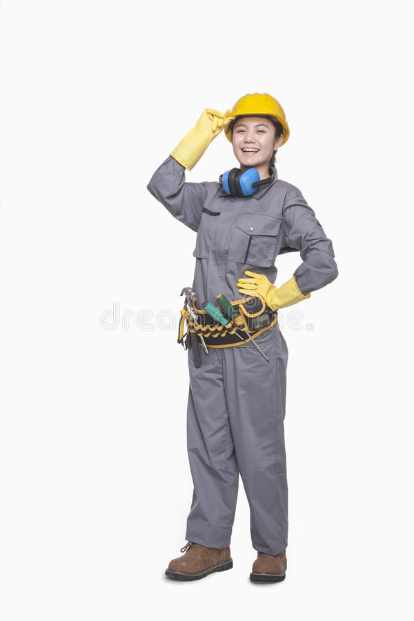Trabalhador da construção fêmea de sorriso com mão no chapéu, retrato, tiro do estúdio fotos de stock