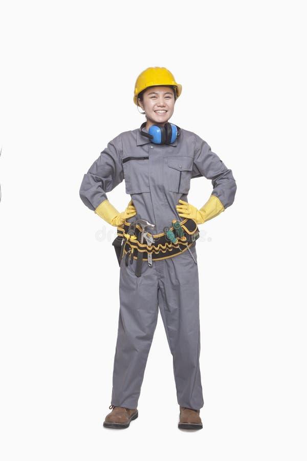 Trabalhador da construção fêmea de sorriso com mãos nos quadris, retrato, tiro do estúdio imagens de stock royalty free