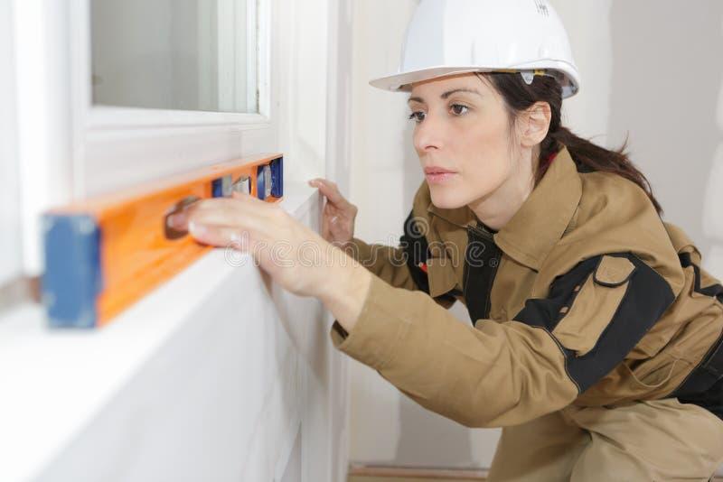 Trabalhador da construção fêmea que instala janelas fotografia de stock royalty free