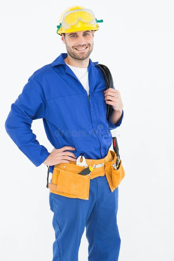 Trabalhador da construção feliz que está com mão no quadril imagem de stock