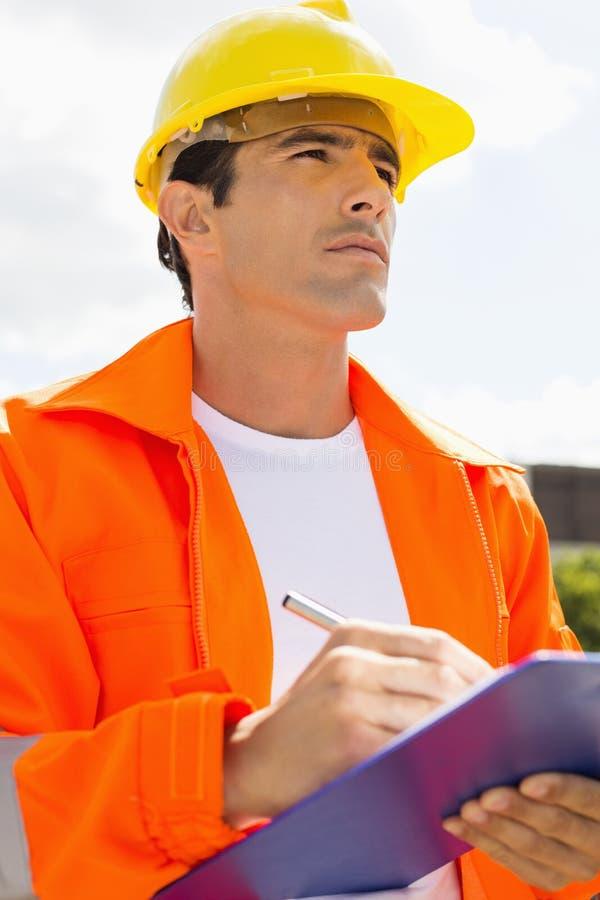 Trabalhador da construção masculino com a prancheta que olha a parte externa ausente fotos de stock