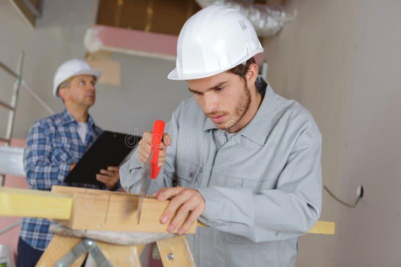 Trabalhador da construção masculino que corta a madeira com handsaw fotografia de stock royalty free