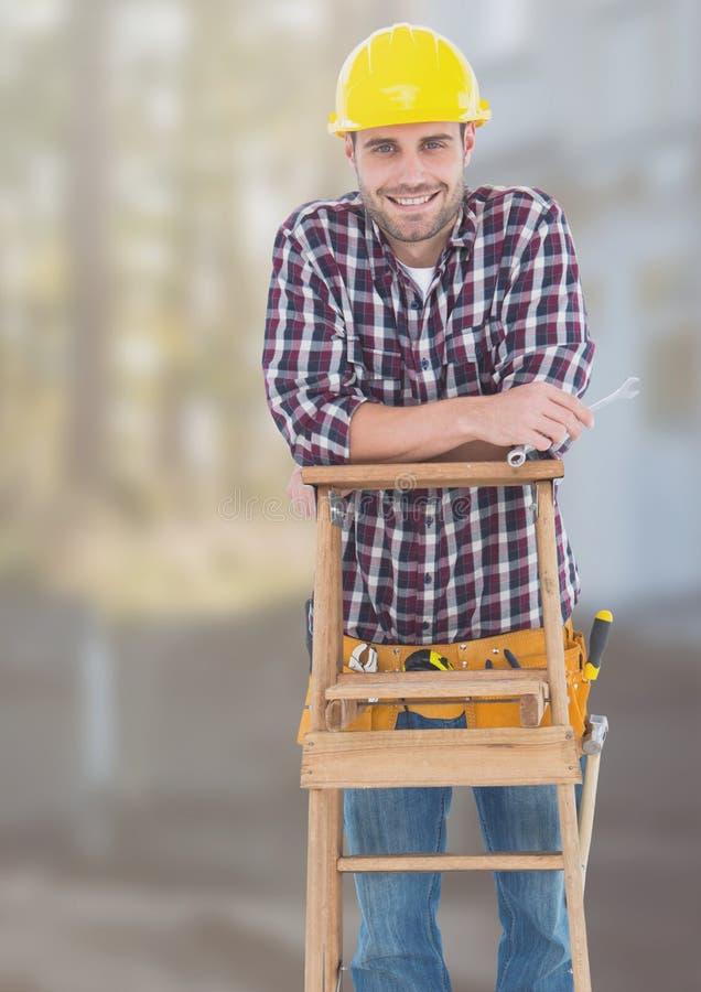 Trabalhador da construção na escada na frente do canteiro de obras fotografia de stock