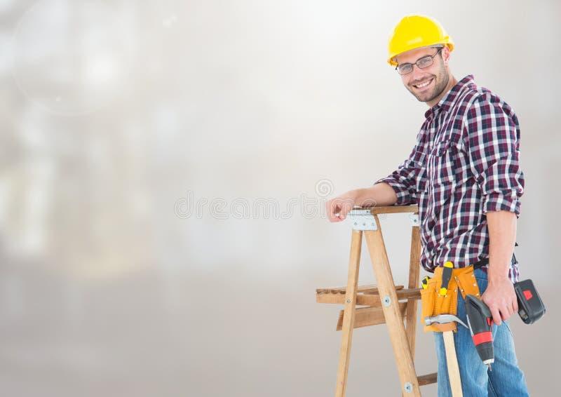 Trabalhador da construção na escada na frente do canteiro de obras foto de stock royalty free