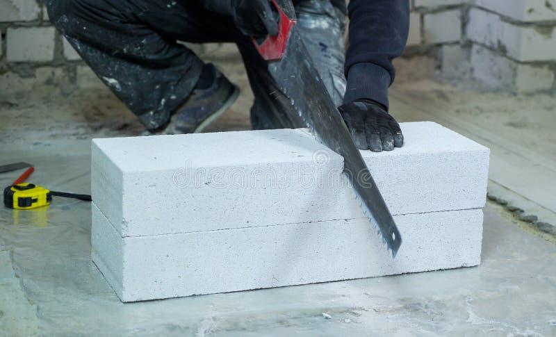 Trabalhador da construção nas luvas que veem o bloco de cimento ventilado fotos de stock royalty free