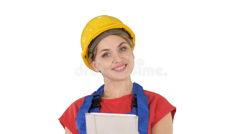 Trabalhador da construção novo com o tablet pc que apresenta algo no fundo branco imagem de stock