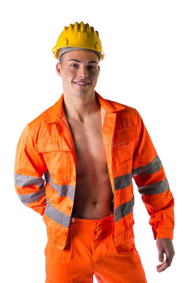 Trabalhador da construção novo de sorriso com o terno alaranjado no torso despido foto de stock