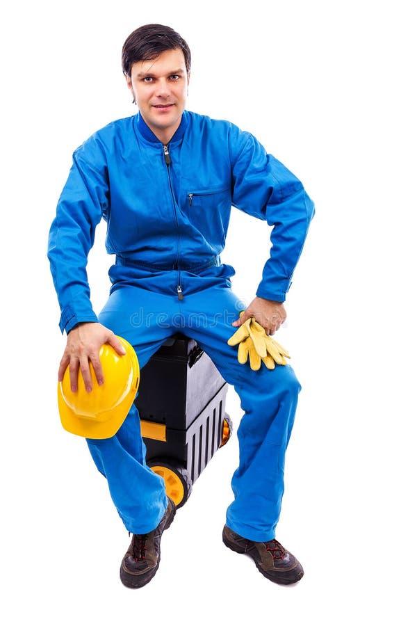 Trabalhador da construção novo que senta-se em sua caixa de ferramentas fotos de stock