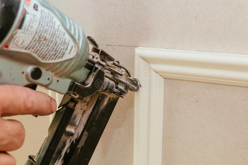 Trabalhador da construção pregado acima da parede do molde da imagem na casa nova fotografia de stock royalty free