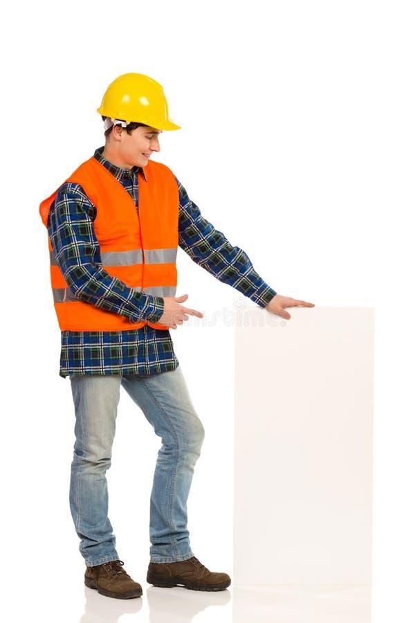 Trabalhador da construção que aponta no baner branco. imagens de stock royalty free