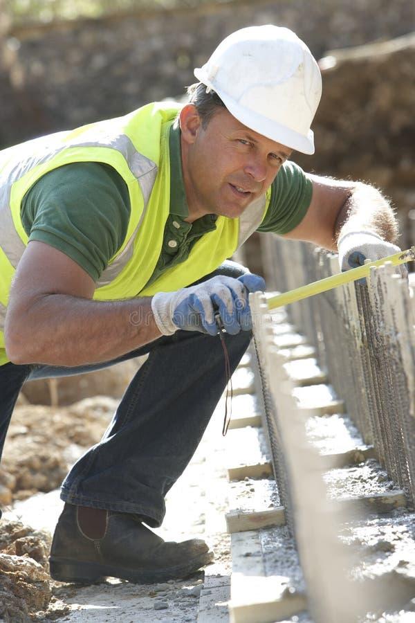 Trabalhador da construção que coloca fundações foto de stock