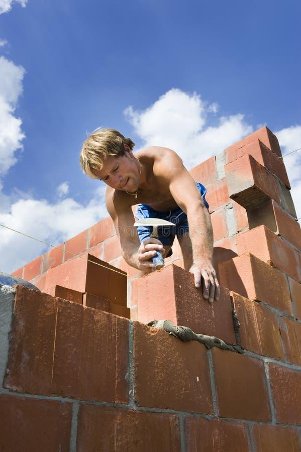 Trabalhador da construção que constrói uma parede imagem de stock