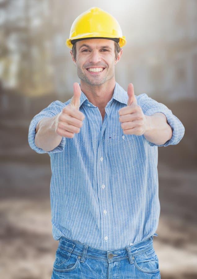 Trabalhador da construção que dá os polegares acima na frente do canteiro de obras imagens de stock royalty free