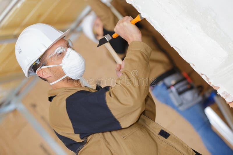 Trabalhador da construção que demole a parede velha com formão imagem de stock royalty free