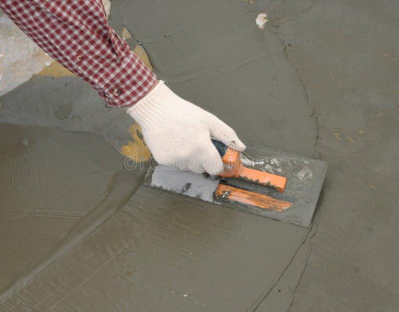 Trabalhador da construção que espalha o concreto molhado imagens de stock
